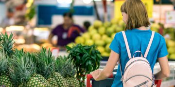 a woman taking a look through some pineapples in a supermarket