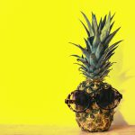 sunglasses on pineapple on yellow background
